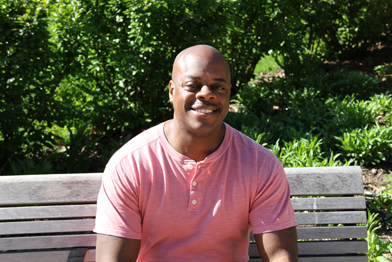 Tryone Patterson, a psychiatric social worker and mental health survivor, sitting on a park bench.